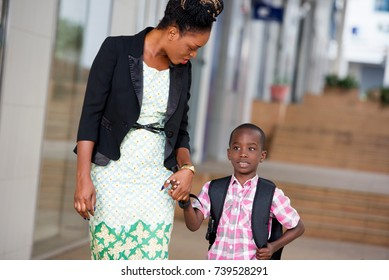 Young woman holding the hand of her schoolboy son gives him some advice on the road.