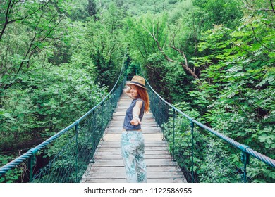 Young woman holding hand on the bridge, leading to adventure