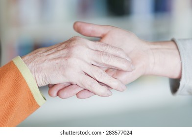 Young woman holding a hand of a senior citizen.
