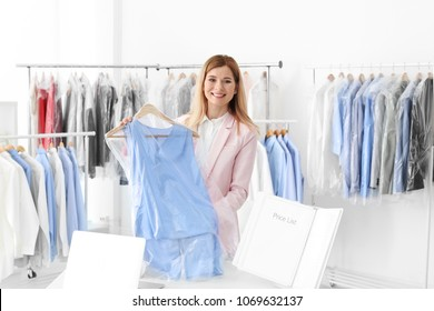 Young woman holding hanger with dress in plastic bag at dry-cleaner's