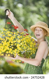 Young woman holding a hanging flower basket and smiling