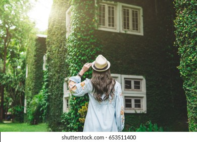 young woman holding hat with green nature background,travel and vacation in green season concept,vintage tone and sun flare effect