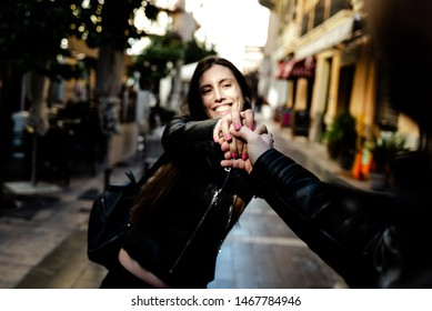 Young woman holding her boyfriend's hand while pulling him through the streets of a city.