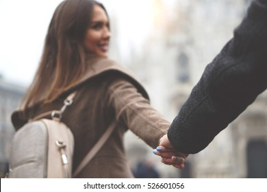 Young woman holding her boyfriend's hand who is following her in the city center - Couple in love traveling - Duomo of Milan in the background - Focus on couple's hands