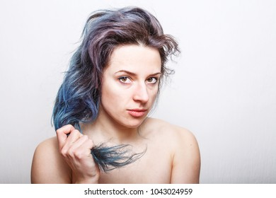 Young woman holding her damaged hair colored in various colors in her hand