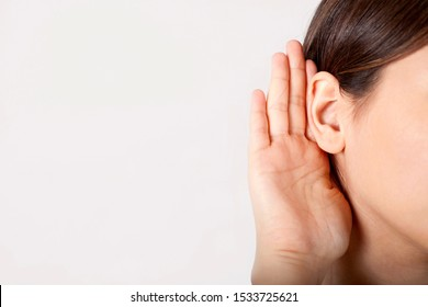 young woman holding her ear to listen