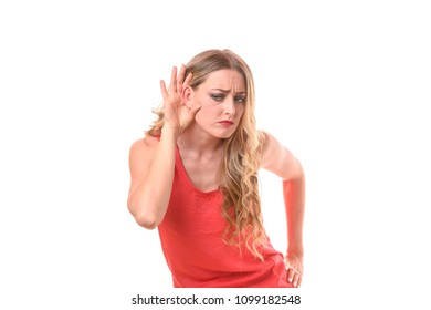 Young woman holding her hand to her ear with a frown of concentration as she pretends she cannot hear or because she is hard of hearing isolated on a white studio background