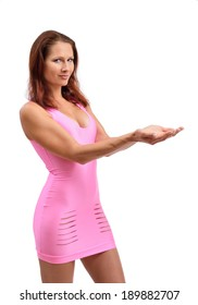 A young woman is holding her hands together. She is wearing a pink sheath short dress.