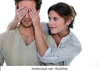 Young woman holding her hands over a man's eyes