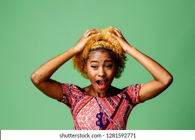 Young woman holding her head with mouth open in disbelief and shock, isolated on green studio background