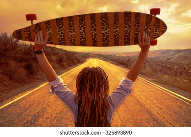 young woman holding her longboard overhead looking downhill during sunrise or sunset with a toned instagram filter