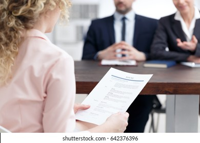Young woman holding her resume during job interview