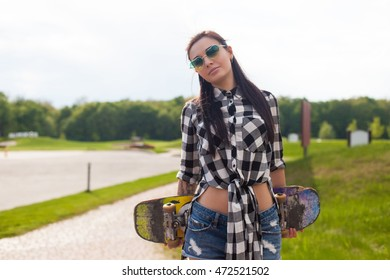 Young woman is holding her skate behind on the background of park.