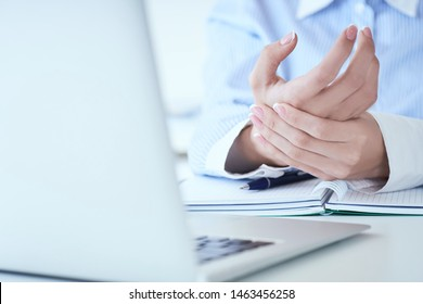 Young woman holding her sore hand on wrist close-up. Pain from using computer. Office syndrome hand pain by occupational disease.