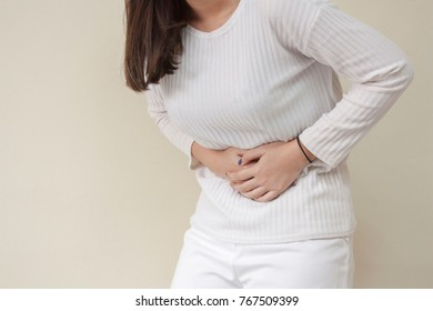 Young Woman holding her stomach. Concept of Stomachache, Painful.
