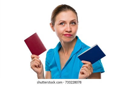 Young Woman is holding her Two, Old and New, Passports or IDs. Positive face emotion with lips smirk. Looking thoughtfully to the side away. Isolated white background.