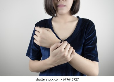 Young woman holding her wrist pain