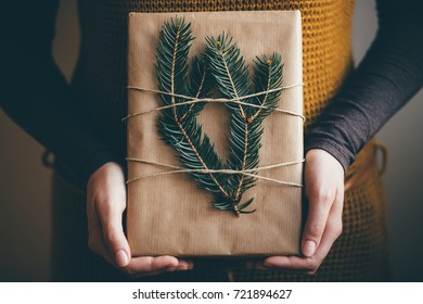 Young woman holding hip cool Christmas present