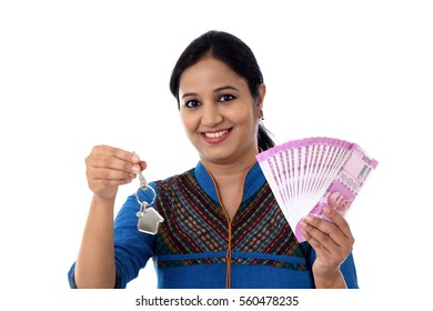 Young woman holding house shape key and 2000 rupee notes
