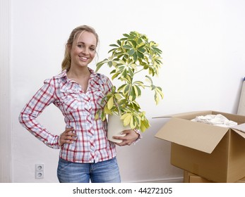 Young woman holding a houseplant with opened moving boxes in a white room.