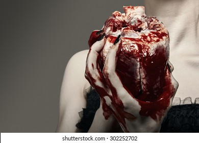 Young woman holding a human heart