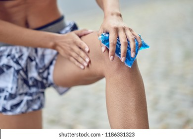 Young woman holding an ice pack to her knee after injuring herself during an outdoors workout in a health and fitness concept