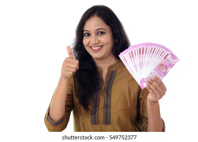 Young woman holding Indian 2000 rupee notes with thumb up gesture