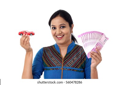 Young woman holding indian currency and toy car against white background