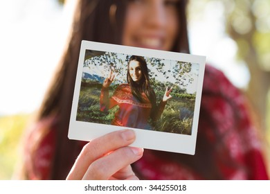 Young woman holding an instant photo print where she is happy