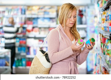 Young woman holding jar in the supermarket with people in the background