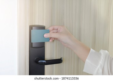 Young woman holding a keycard openning hotel door