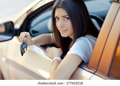 Young woman holding keys to new car and smiling at camera