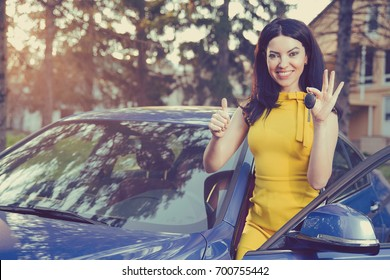 Young woman holding keys to new car smiling showing thumbs up on a background of a house