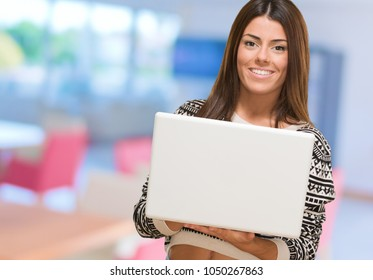 Young Woman Holding Laptop at an office