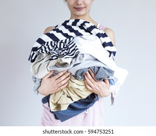 Young woman holding laundry on gray background