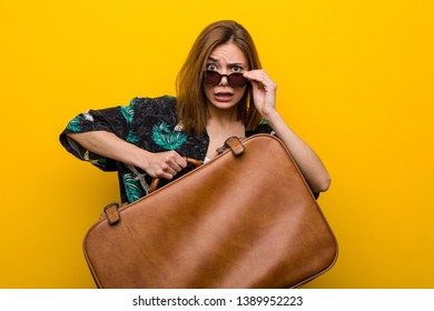 Young woman holding a leather bag  scared about her vacations, s