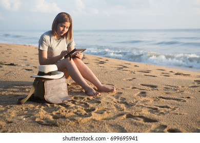 young woman holding and looking at smart phone on a beach