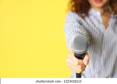 Young woman holding microphone on color background, closeup with space for text