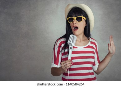 Young woman holding a microphone singing on gray background
