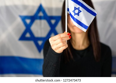 Young Woman Holding Mini Israel Flag In Front Of Face on Israeli Flag Background.