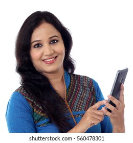 Young woman holding mobile phone against white background