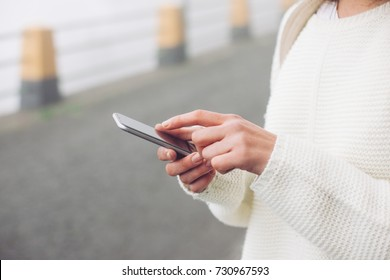 Young woman holding mobile phone on the road in fog close-up.