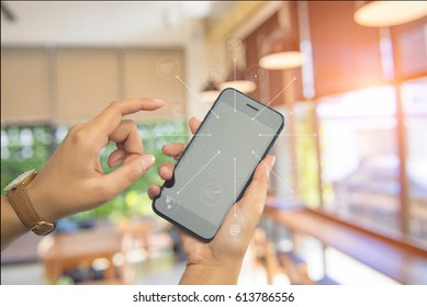 Young woman holding mobile smart phone and background Blur cafe shop, Blur restaurant with application development