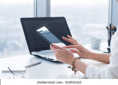 Young woman holding modern tablet computer, using device at workplace during break, chatting, blogging and posting information with apps.