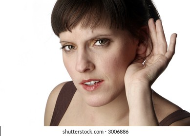 a young woman is holding one hand to her ear