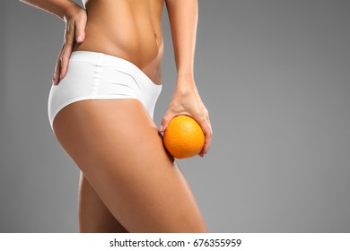Young woman holding orange on grey background. Cellulite problem concept