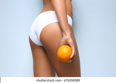 Young woman holding orange on light background. Cellulite problem concept