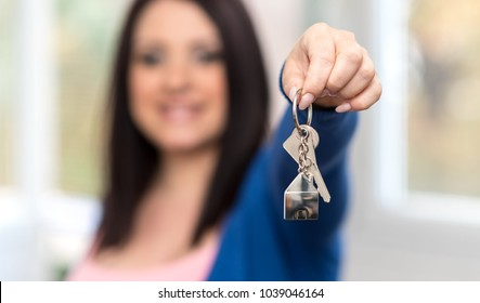 Young woman holding out house keys