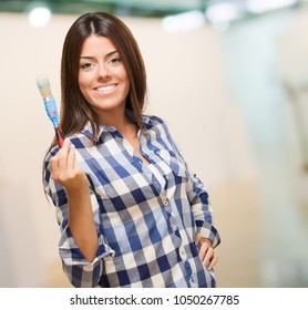 Young Woman Holding Paint Brush, indoor