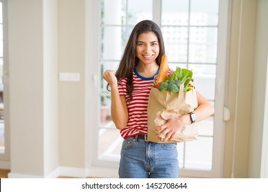 Young woman holding paper bag full of groceries screaming proud and celebrating victory and success very excited, cheering emotion